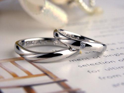 トップで腕が重なったV字型結婚指輪
